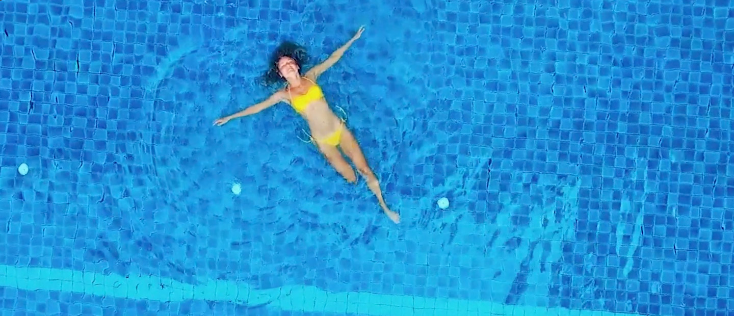 woman butterfly stroke in middle of clear pool