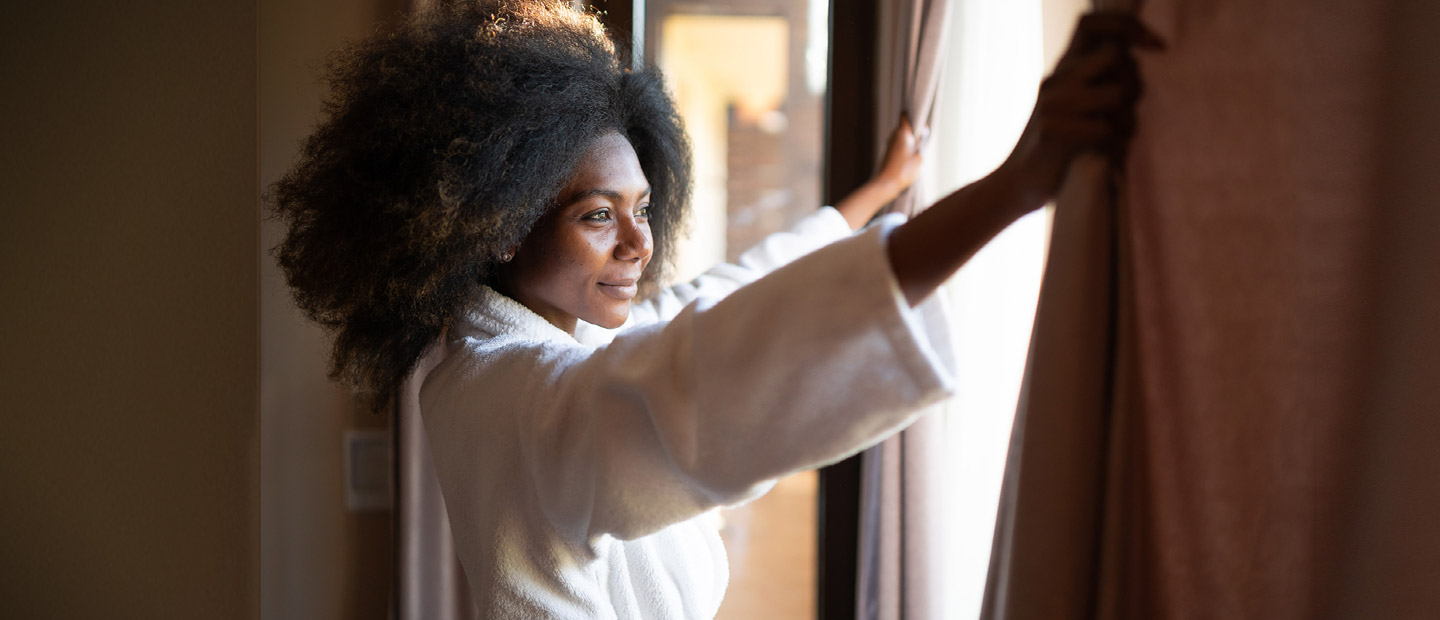 Guest in bathrobe looking out hotel room window
