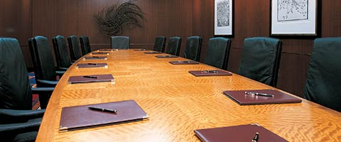 meeting room with wooden long table and black chairs