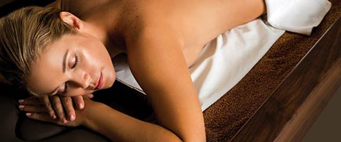 woman laying on spa table with eyes closed